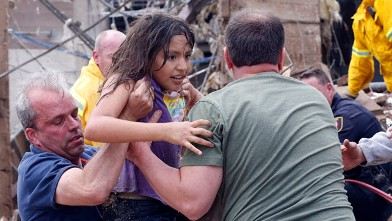 A child is pulled from the rubble of the Plaza Towers Elementary School in Moore, Okla., and passed along to rescuers, May 20, 2013.
