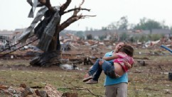 PHOTO: A woman carries her child through a field near the collapsed Plaza Towers Elementary School in Moore, Okla., May 20, 2013.