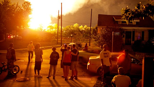 PHOTO: People watch the flames shoot up from a freight train that derailed, early July 11, 2012 in Columbus Ohio.