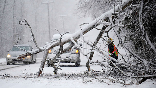 PHOTO: Volunteers remove a downed tree on the road near Chancellorsville, Va. A snowstorm blanketed the Fredericksburg region, March 6, 2013, closing schools, county governments and roads.
