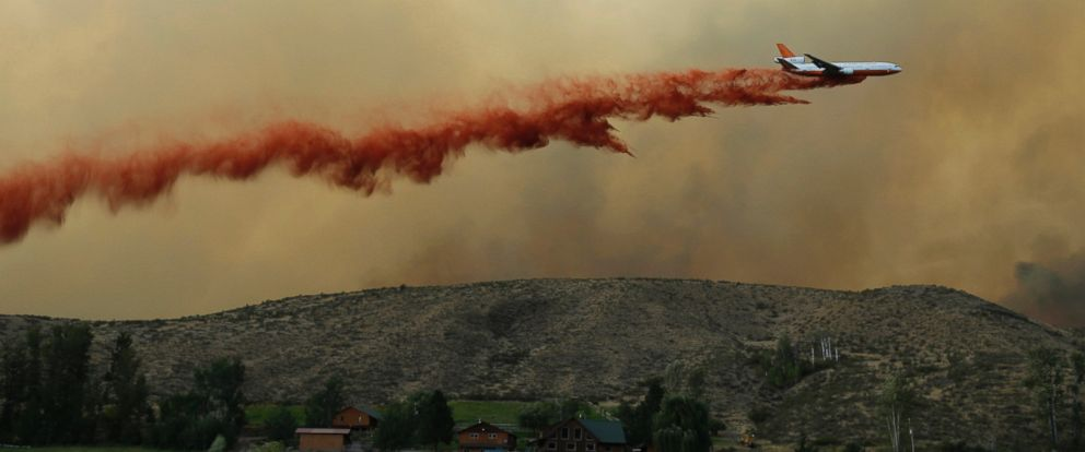 PHOTO: An air tanker drops red fire retardant on a wildfire near Twisp, Wash., Aug. 19, 2015.