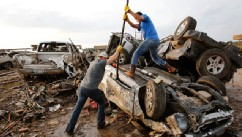 PHOTO: Two men attempt  to pry open a door on this car to check for victims in a business parking lot west of I-35 south of 4th Street  in Moore, on  May 20, 2013.