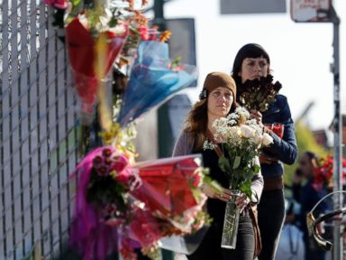 PHOTO: Well-wishers walk to place flowers at the scene in the aftermath of a warehouse fire, Sunday, Dec. 4, 2016, in Oakland, Calif.