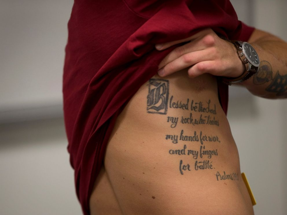 PHOTO: This photo taken May 13, 2014 shows medically retired Marine Lance Cpl. Kyle Carpenter lifting his shirt to show a tattoo on his side as he speaks with media at the Pentagon.