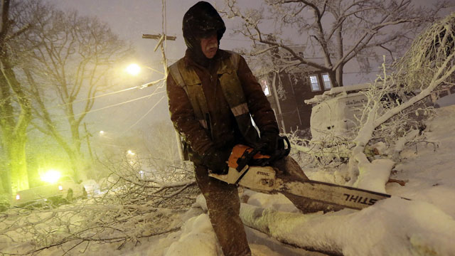 PHOTO: Louie Rodriguez of the New Bedford Forestry Department cuts a fallen tree at the intersection of Rotch St. and Maple St. in New Bedford, Mass., on Friday, Feb. 8, 2013, after heavy snow and winds from a storm.