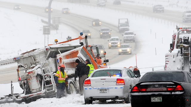 PHOTO: Police and road workers inspect the scene where a snow plow slid off the road along Route C470 in the Denver suburb of Morrison, Colo., Dec. 22, 2011.