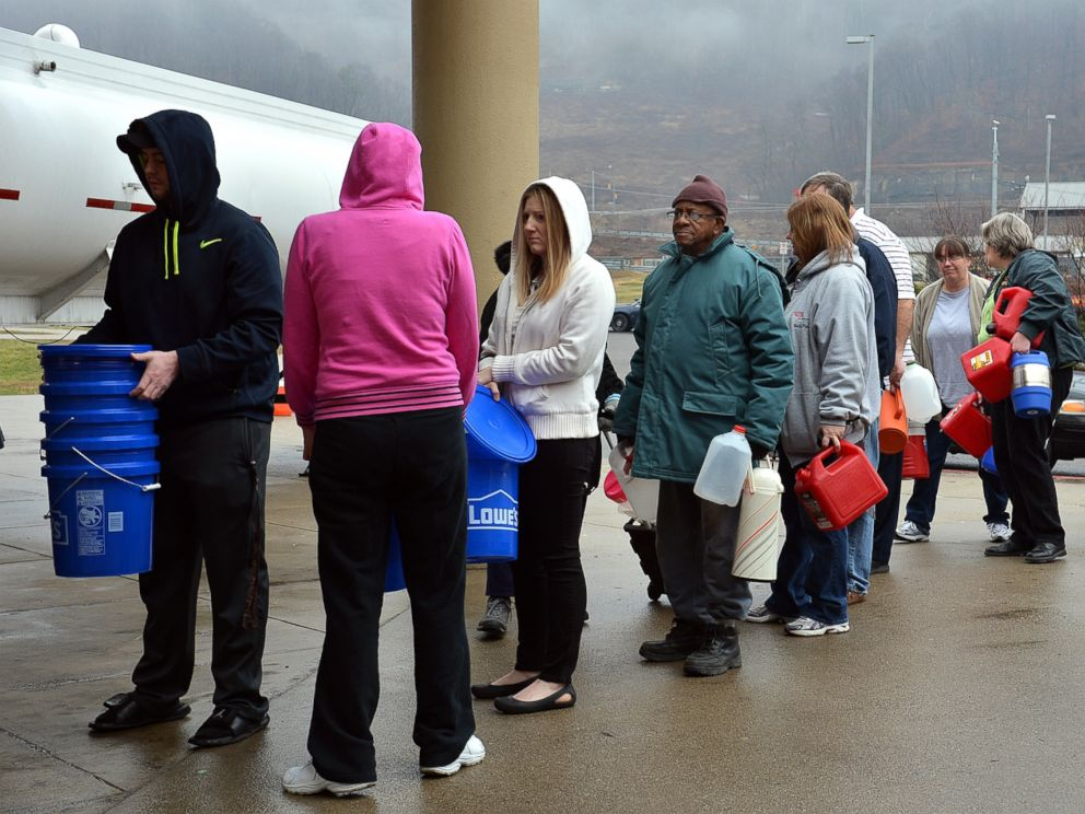 PHOTO: People wait in line for water from a 7500 gallon tanker truck brought in from Washington, Pa., on Jan. 10, 2014, at Riverside High School near Charleston, W.Va.