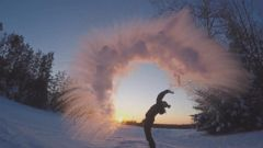 'PHOTO: To display just how cold it actually was, Kerrilyn Esselink, of the Manitou Weather Station Fishing Lodge, threw a mug full of water over her head against the setting sun. The water froze instantly as it was lifted upwards by the wind' from the web at 'http://a.abcnews.com/images/US/boiling-water-cold-weather-01-ht-jrl-171229_16x9t_240.jpg'