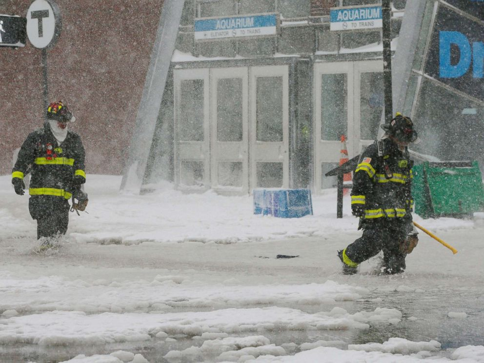 PHOTO: Firefighters wade through a street flooded from tidal surge in Boston, Mass., Jan. 4, 2018.