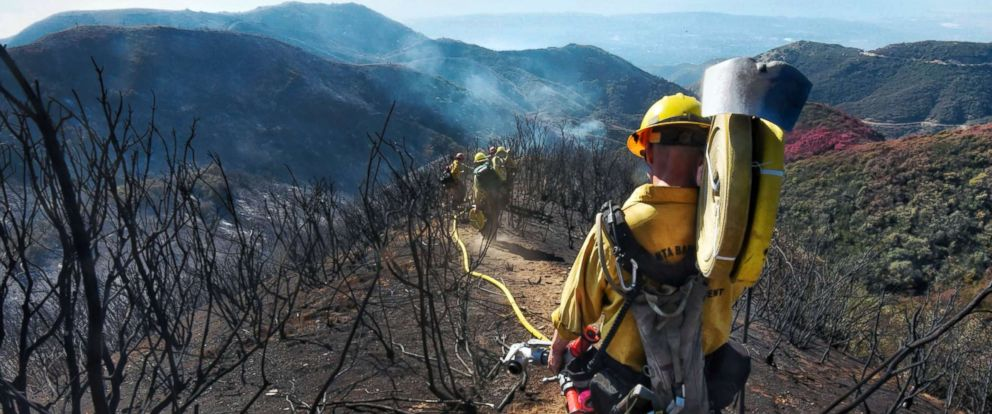 PHOTO: Santa Barbara County Firefighters haul dozens of pounds of hose and equipment down steep terrain below E. Camino Cielo to extinguish smoldering hot spots in Santa Barbara, Calif., on Dec. 19, 2017.