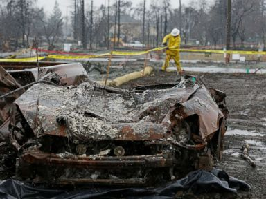 PHOTO: With a burned car in the foreground a worker finishes up erosion control efforts in the wildfire damaged Coffey Park neighborhood, Jan. 8, 2018, in Santa Rosa, Calif.