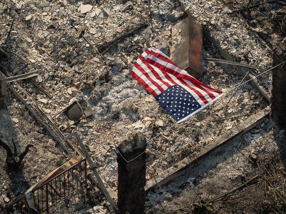 PHOTO: An American flag flies over the remains of a Coffey Park home following the Tubbs fire in Santa Rosa, Calif.