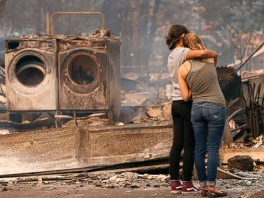 PHOTO: Steph Gediman, left, comforts Brandi Burns in front of Burns destroyed home at the scene of the Tubbs Fire in Santa Rosa, Ca., Oct. 9, 2017.