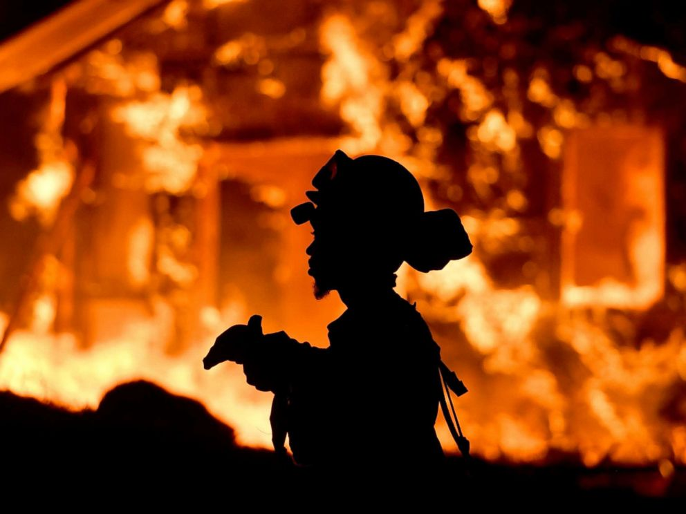 PHOTO: A firefighter monitors flames as a house burns in the Napa wine region in California, Oct. 9, 2017, as multiple wind-driven fires continue to whip through the region.