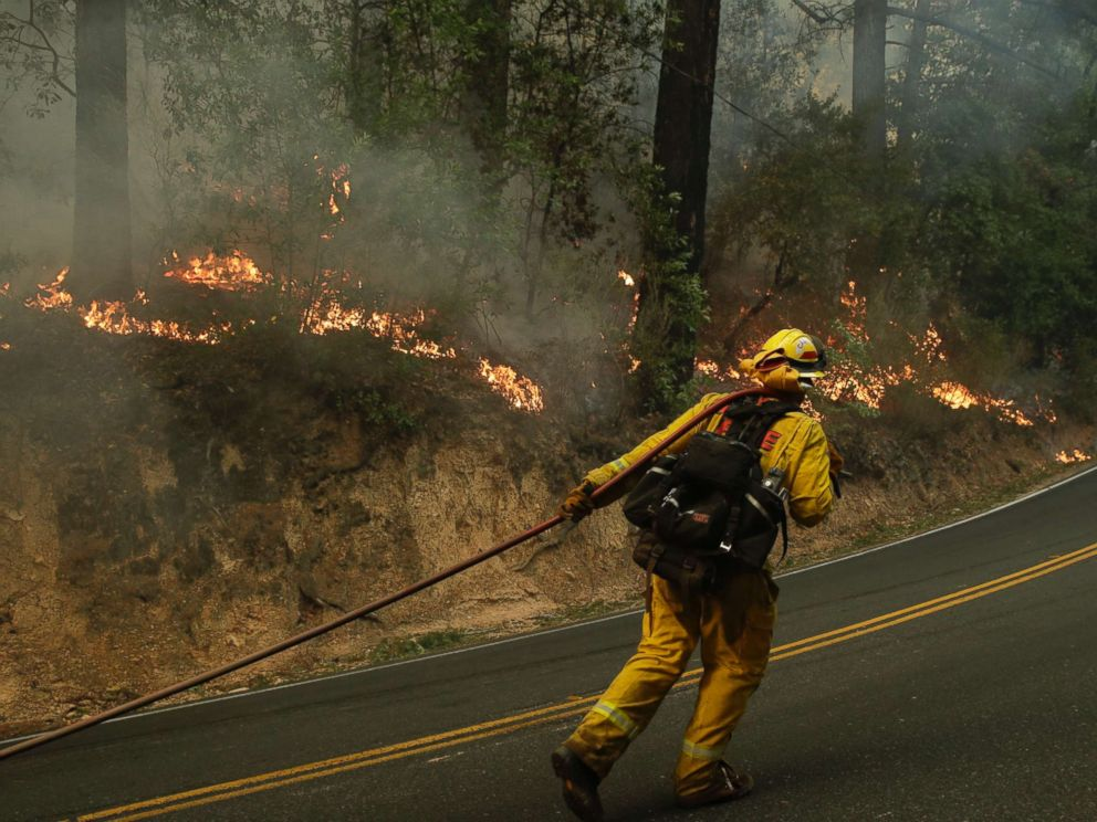 PHOTO: Firefighter David Allhiser carries a water hose to put out a fire, Oct. 12, 2017, near Calistoga, Calif.