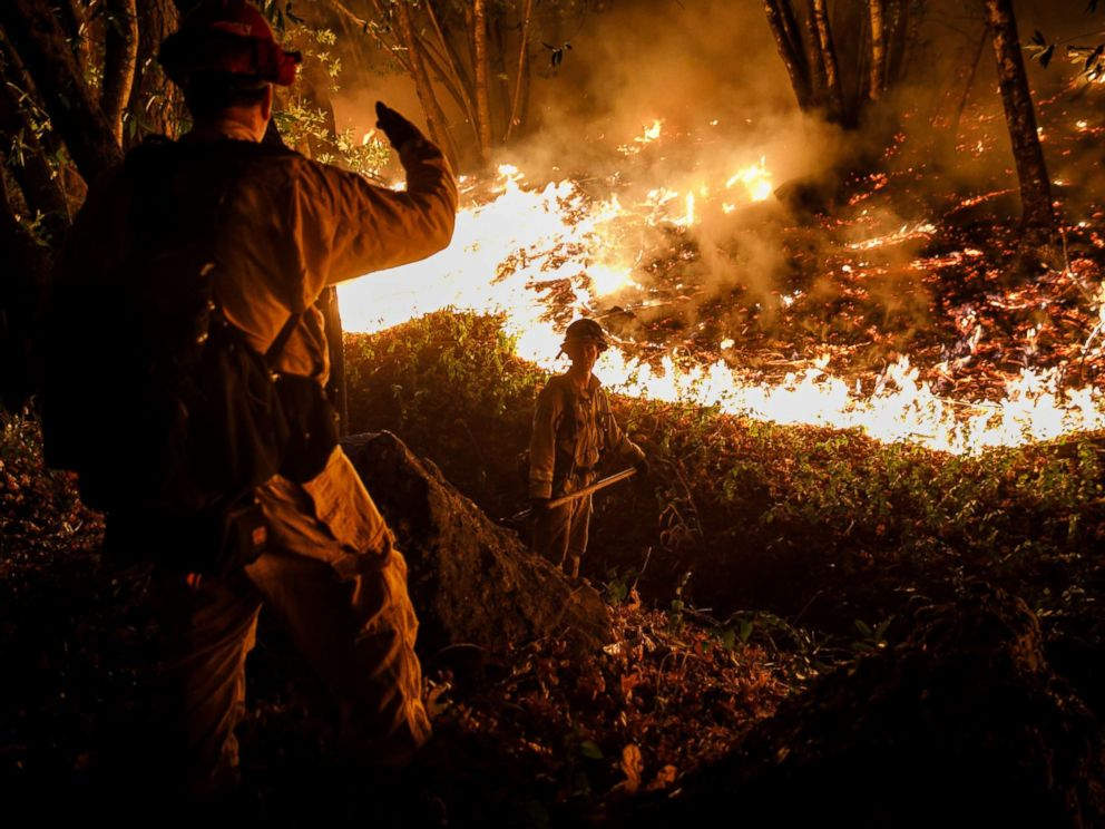 PHOTO: CALFIRE firefighter Tim Zanotelli, center, receives instructions from Captain Gary Mattingly, left, while performing a firing operation to prevent the flames from crossing Highway 29, north of Calistoga, Calif., Oct. 12, 2017.