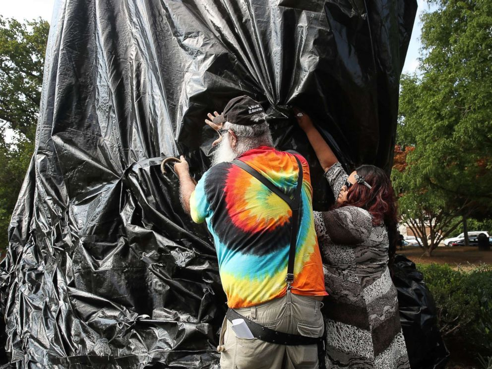 PHOTO: A women tries to stop John Miska from cutting off the black tarp that was put over the statue of Confederate Gen. Robert E. Lee that stands in the center of Emancipation Park, formerly Lee Park, on Aug. 23, 2017 in Charlottesville, Va.