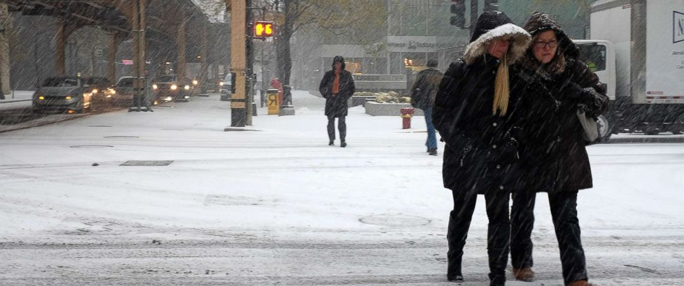 PHOTO: Pedestrians cross the street as the snow falls, Nov. 10, 2017, in downtown Chicago.