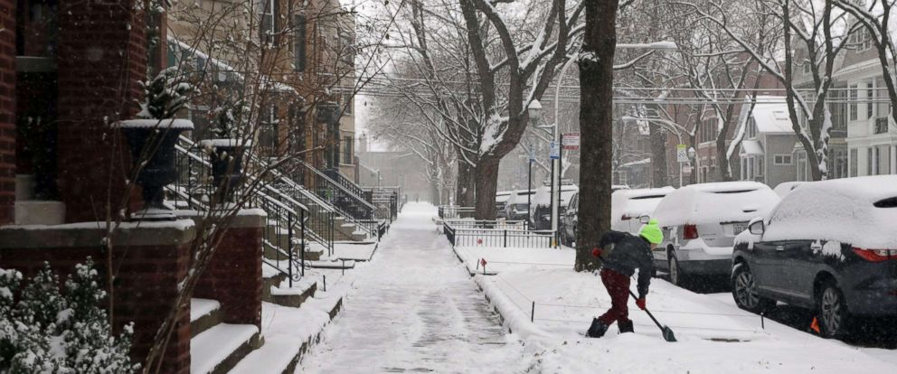 PHOTO: A young child is seen shoveling snow in the Lakeview neighborhood of Chicago, Dec. 24, 2017.
