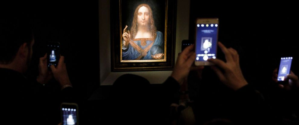 PHOTO: People take pictures of the painting Salvator Mundi by Leonardo da Vinci (circa 1500) during a public preview before an auctioning of the painting tonight at Christies auction house in New York, Nov. 15, 2017.