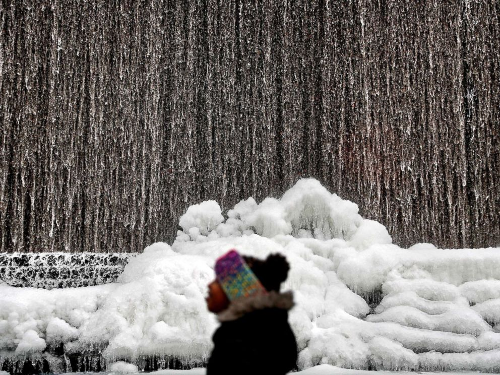 PHOTO: Alora Freeman, 8, watches as ice builds along a downtown water fountain in Atlanta, Jan. 3, 2018.
