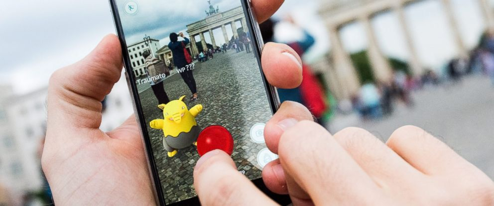 "PHOTO: A picture made available on July 14, 2016 shows man trying to catch a pokemon called ""Drowzee"" in the ""Pokemon Go"" augmented reality game in Berlin, Germany."