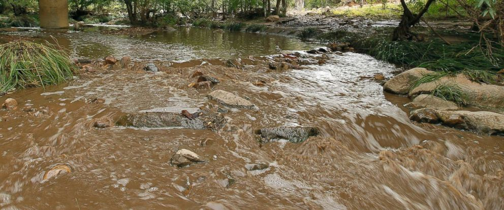 PHOTO: Muddy floodwaters of the East Verde River flow under a bridge where one victim of the flash flood was found during a search and rescue operation by the Gila County Sheriffs Office, July 16, 2017, in Payson, Ariz.