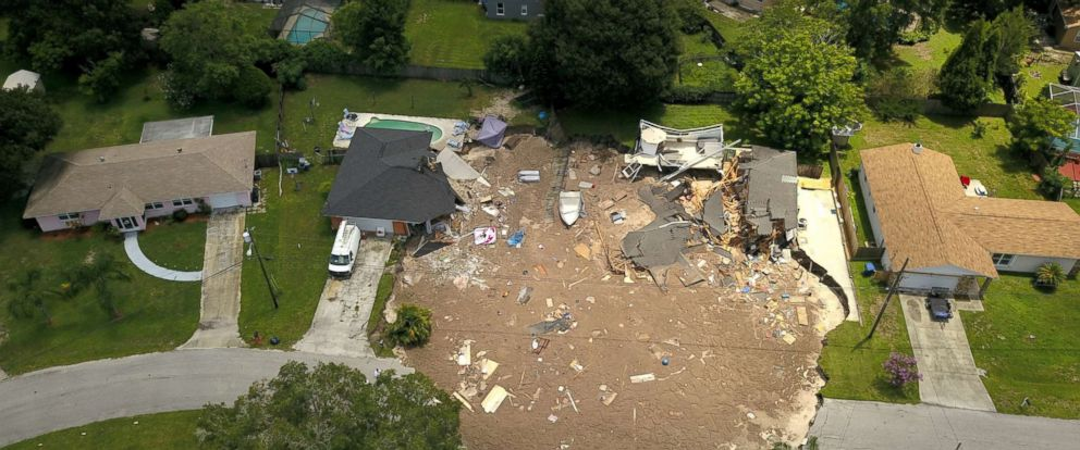 PHOTO: Debris is strewn about after a sinkhole damaged two homes in Land O Lakes, Fla.