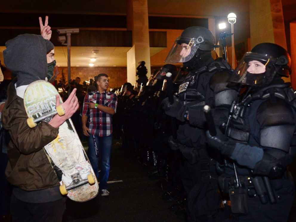 PHOTO: A protestor gestures at police at Pioneer Square in Portland, Oregon on November 11, 2016, to protest the election of US President-elect Donald Trump.