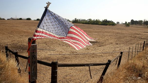 PHOTO: An American flag is posted on a fence in front of a dry unplanted field on Aug. 8, 2014 in Lodi, Calif.