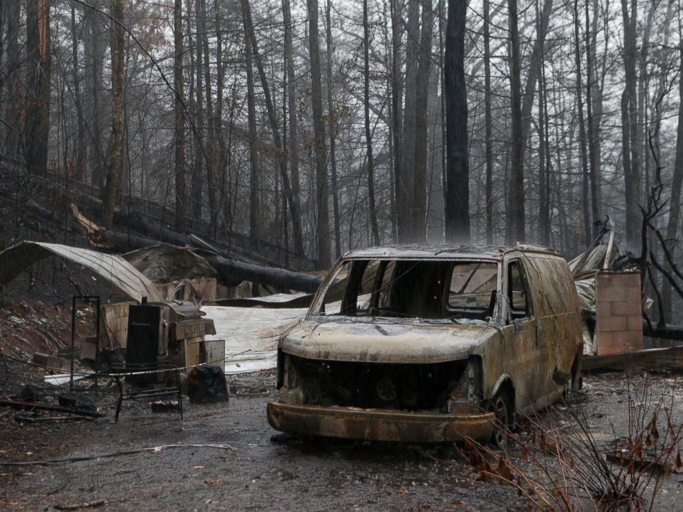PHOTO: The remains of a van and home smolder in the wake of a wildfire, Nov. 30, 2016 in Gatlinburg, Tennessee.