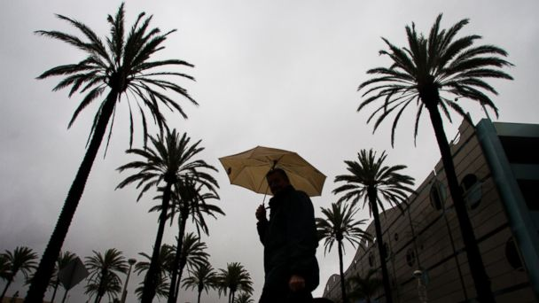 PHOTO: A pedestrian ducks under an umbrella while heading to work in Long Beach as a major storm bears down on Southern California, bringing with it fears of heavy rainfall, flash floods and debris flows in the Southland Friday, Dec. 12, 2014.