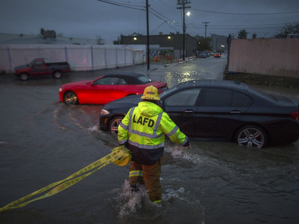 PHOTO: A firefighter carries caution tape in a flooded street as a powerful storm moves across Southern California Feb. 17, 2017, in Sun Valley, California.