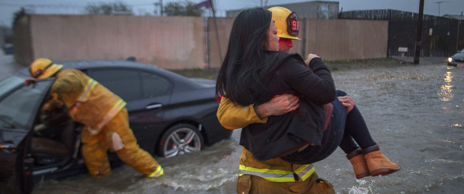 PHOTO: A firefighter carries a woman from her car after it was caught in street flooding as a powerful storm moves across Southern California, Feb. 17, 2017, in Sun Valley, California.