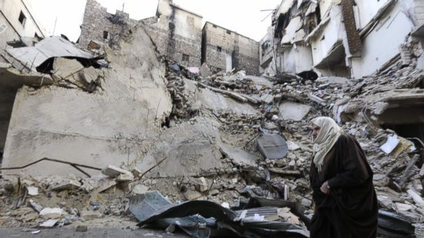 PHOTO: A Syrian woman walks past a destroyed building in Aleppo's formerly rebel-held al-Shaar neighborhood, Jan. 21, 2017, a month after government forces retook the northern Syrian city from rebel fighters.