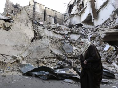 PHOTO: A Syrian woman walks past a destroyed building in Aleppos formerly rebel-held al-Shaar neighborhood, Jan. 21, 2017, a month after government forces retook the northern Syrian city from rebel fighters.