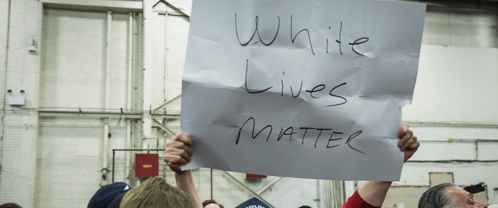 "PHOTO: A Trump supporter holds up a ""White Lives Matter"" sign during a rally for Republican Presidential Candidate Donald Trump on April 6, 2016 in Bethpage, New York."