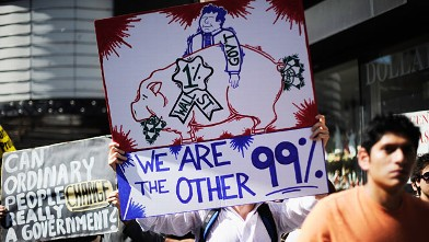 "PHOTO: Protesters hold signs as they march in solidarity with the ongoing ""Occupy Wall Street"" protest."