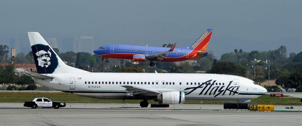 PHOTO: A Southwest Airlines Boeing 737 passenger jet lands as an Alaska Air Boeing 737 jet prepares to take off at Los Angeles International Airport on April 5, 2011.