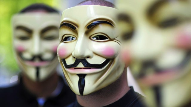 "PHOTO: Activists of the organization ""Anonymous"" hold masks in front of their faces during a demonstration in Berlin."