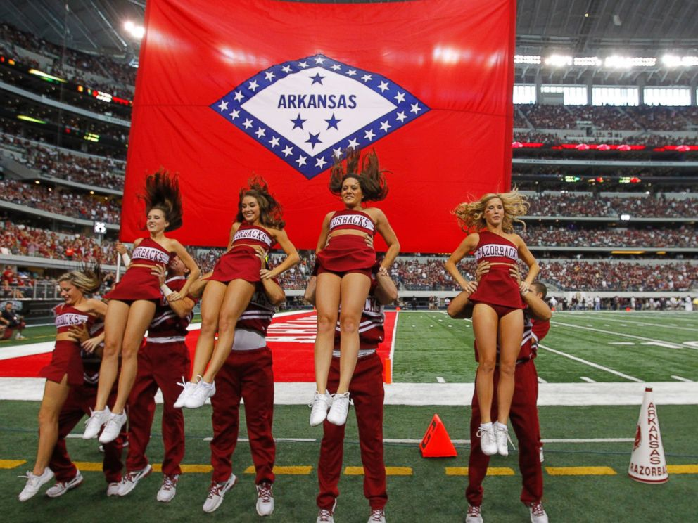 PHOTO: Arkansas cheerleaders perform a routine in front of their state flag at Cowboys Stadium in Arlington, Texas, on Oct. 1, 2011.