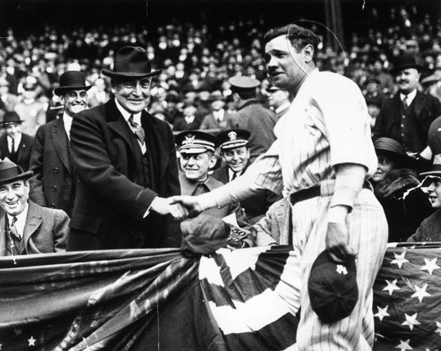 Babe Ruth throws his Babe Ruth candy bars to the fans sitting in the ...