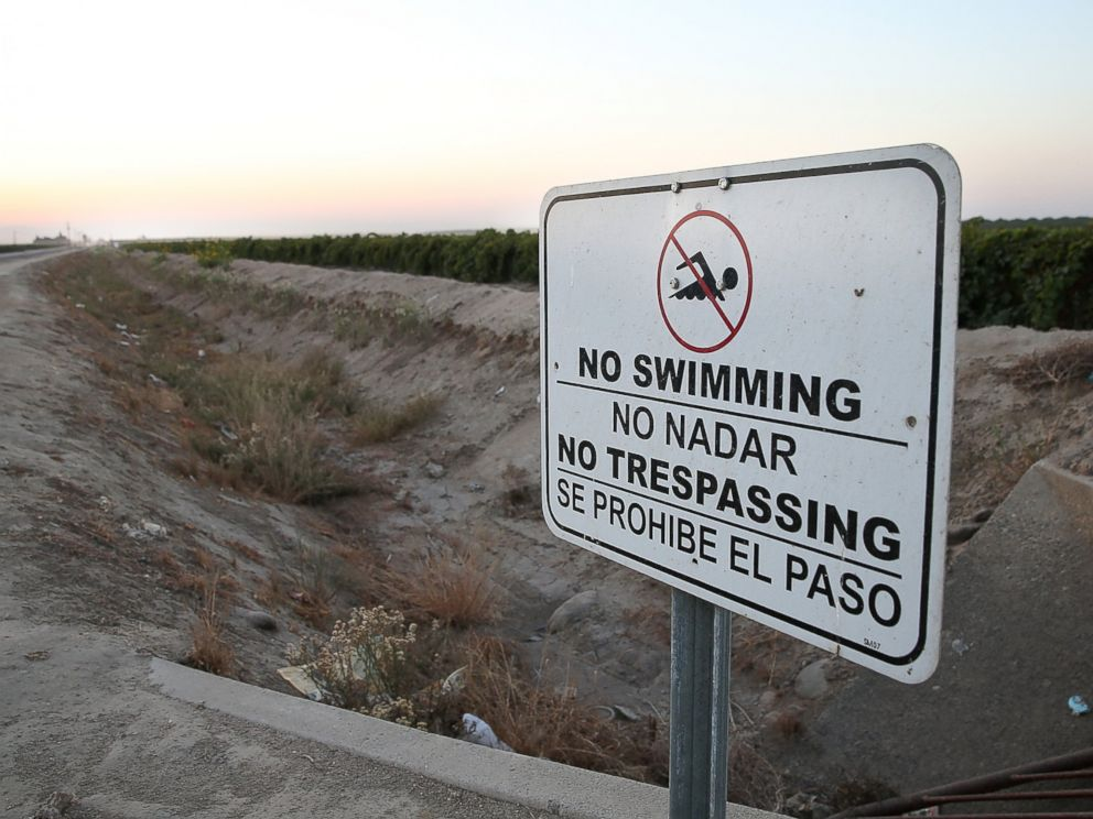 PHOTO: A no swimming sign is posted next to a dry irrigation canal on August 22, 2014 in Madera, California.