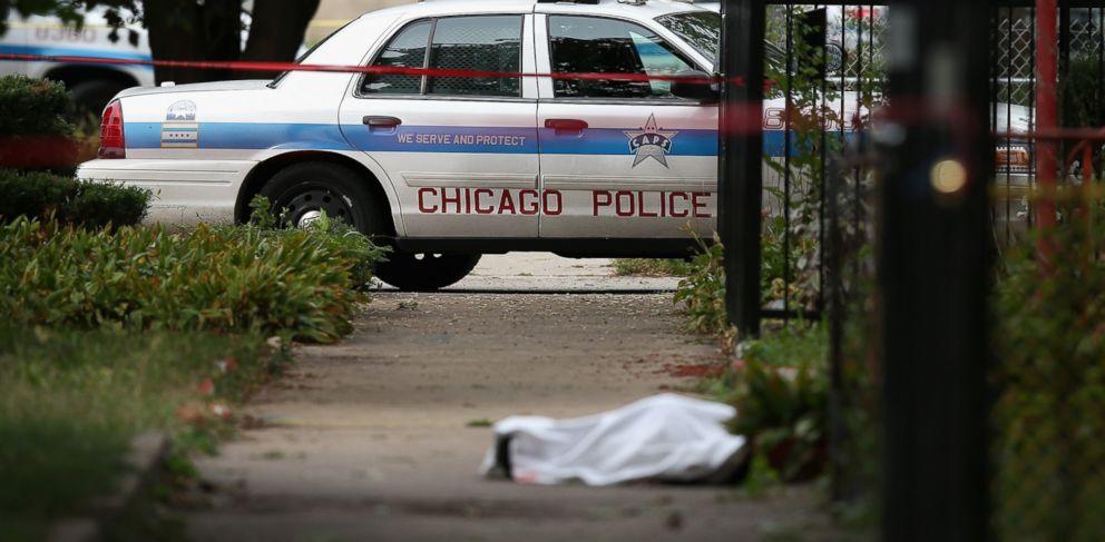 PHOTO: Police investigate the shooting death of 14-year-old Tommy McNeal, whose body is covered by a sheet on the sidewalk on September 20, 2013 in Chicago, Illinois.
