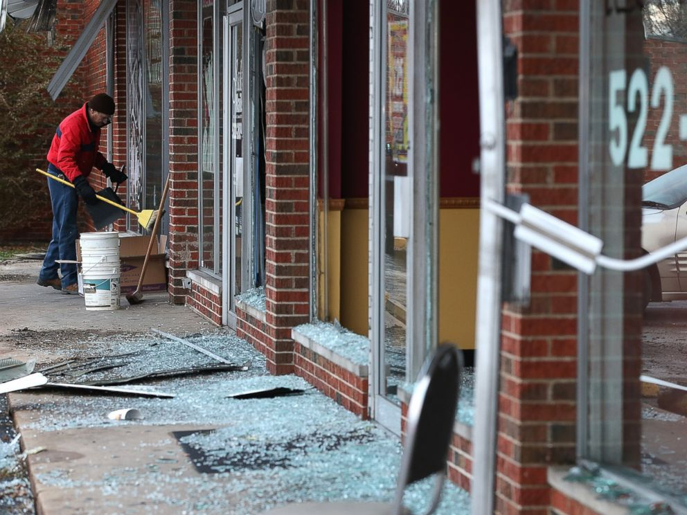PHOTO: A worker cleans up glass at a building that was damaged during a demonstration on Nov. 25, 2014 in Dellwood, Mo.