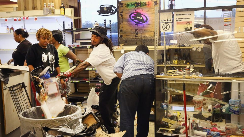 PHOTO: Voluteers help the owners of Sams Meat Market clean up after their business was looted during another night of rioting following protests over the shooting death of Michael Brown on August 16, 2014 in Ferguson, Missouri.