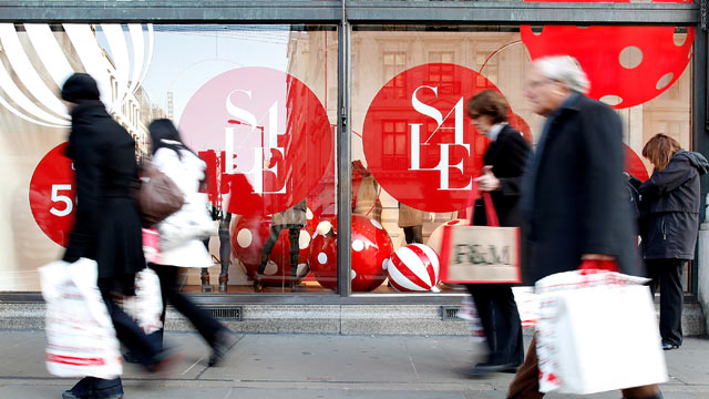 PHOTO: Pedestrians walk past a store window advertising Christmas sales discou