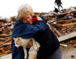 PHOTO: June Simson receives a hug from her neighbor while embracing her cat Sammi after she found him standing on the rubble of her destroyed home, May 21, 2013 in Moore, Okla.