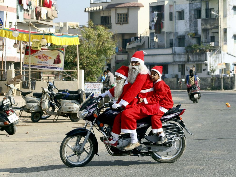 PHOTO: An Indian man and a pair of children dressed as Santa Claus ride a motorcycle along a street of Ahmedabad, December 21, 2006.