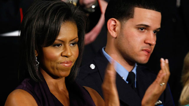 PHOTO: Michelle Obama applauds her husband, President Barack Obama, while he addresses a joint meeting of Congress as Philadelphia Police Officer Richard DeCoatsworth, right, stands by